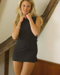 Woman in little dress, tan satin sheer pantyhose and black boots
