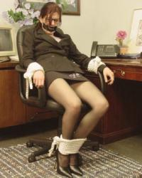 Secretary with glasses in suit and black pantyhose tied up and gagged